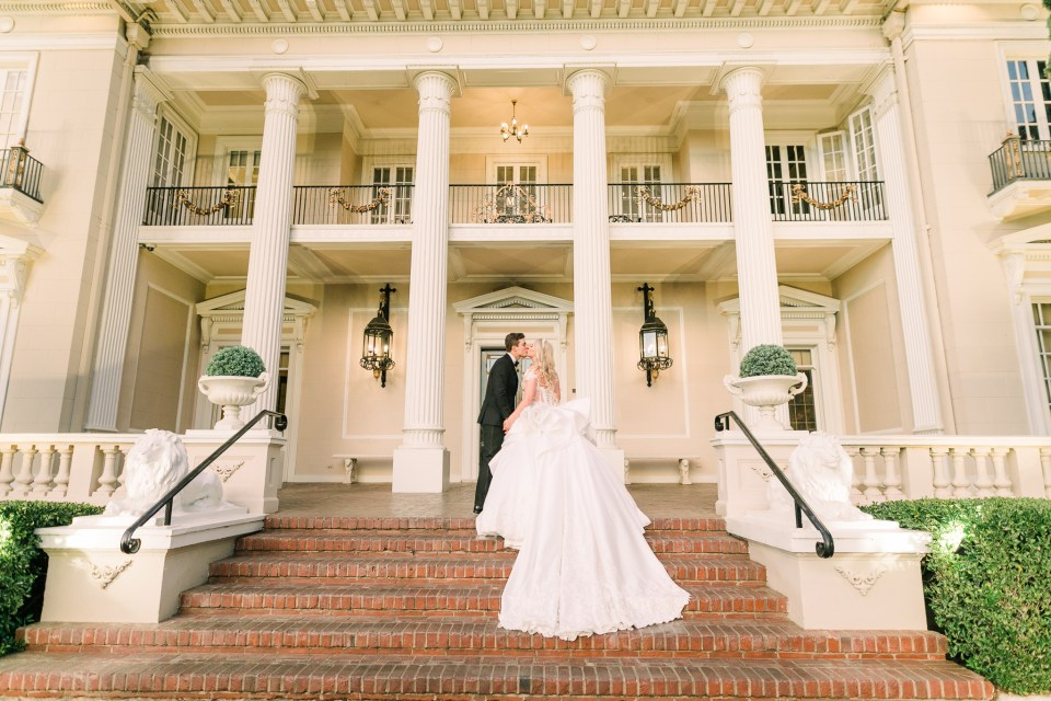a couple kisses on the steps at their Grand Island Mansion wedding