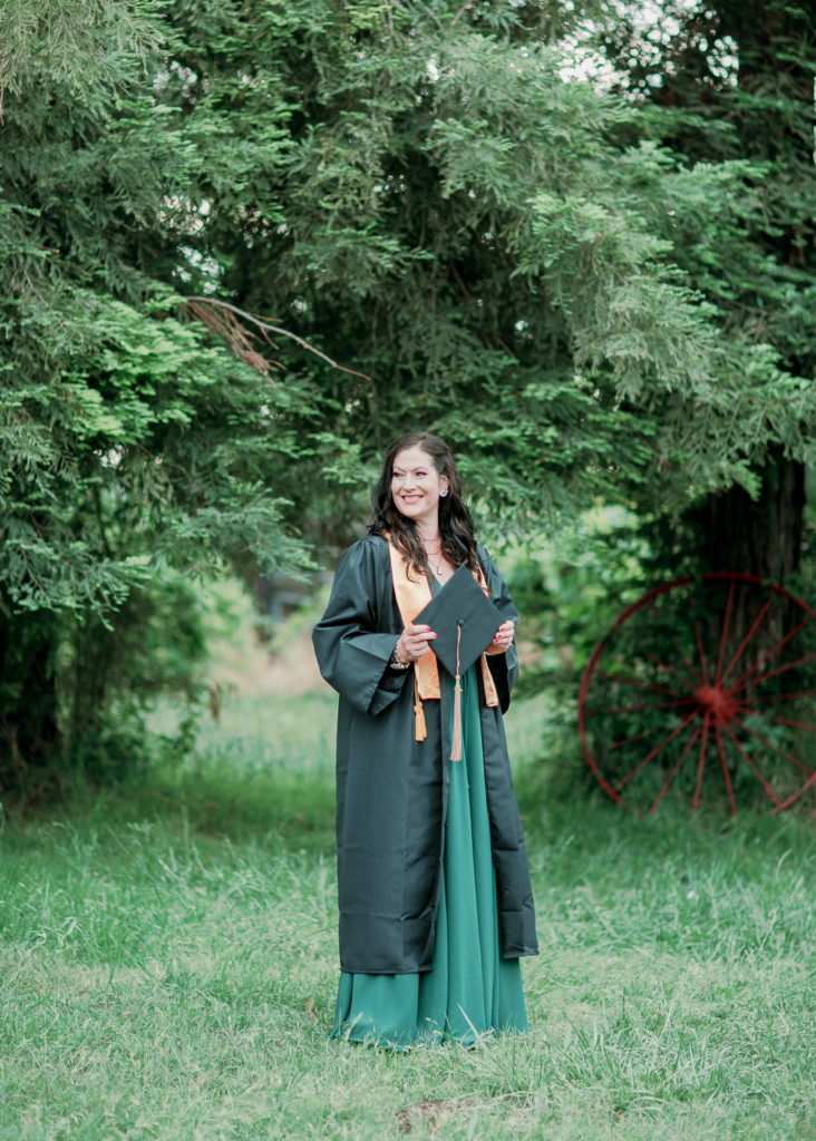 a woman poses for grad photos while wearing her cap and gown