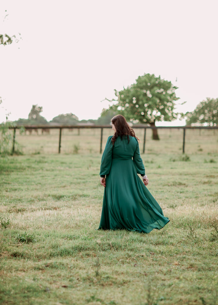 a woman twirls in a green dress during her grad photos