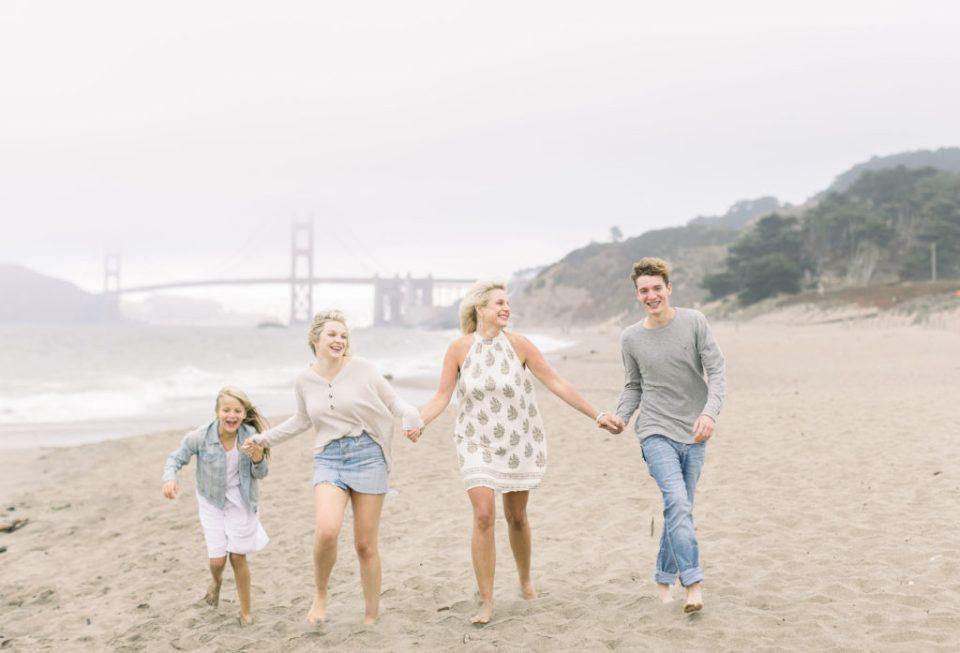 a family runs at Baker Beach for tips for beach photos