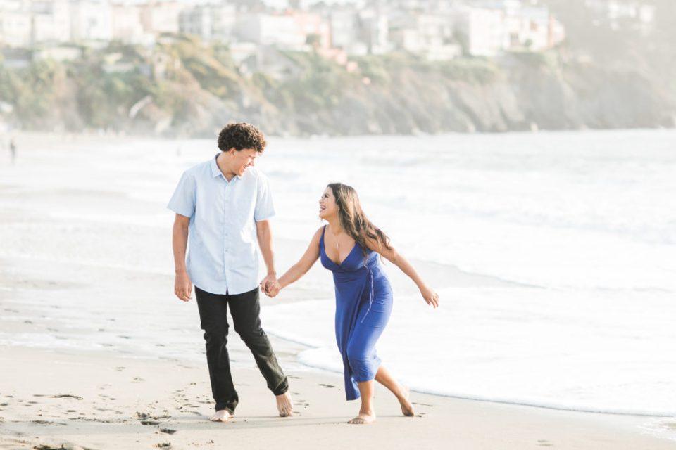two high school seniors run along Baker Beach during photos celebrating being a teen in 2020