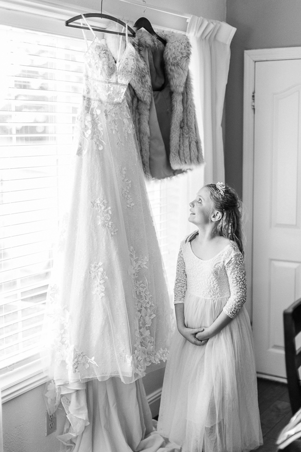 a flower girl admires a wedding gown before a Bay Area intimate wedding