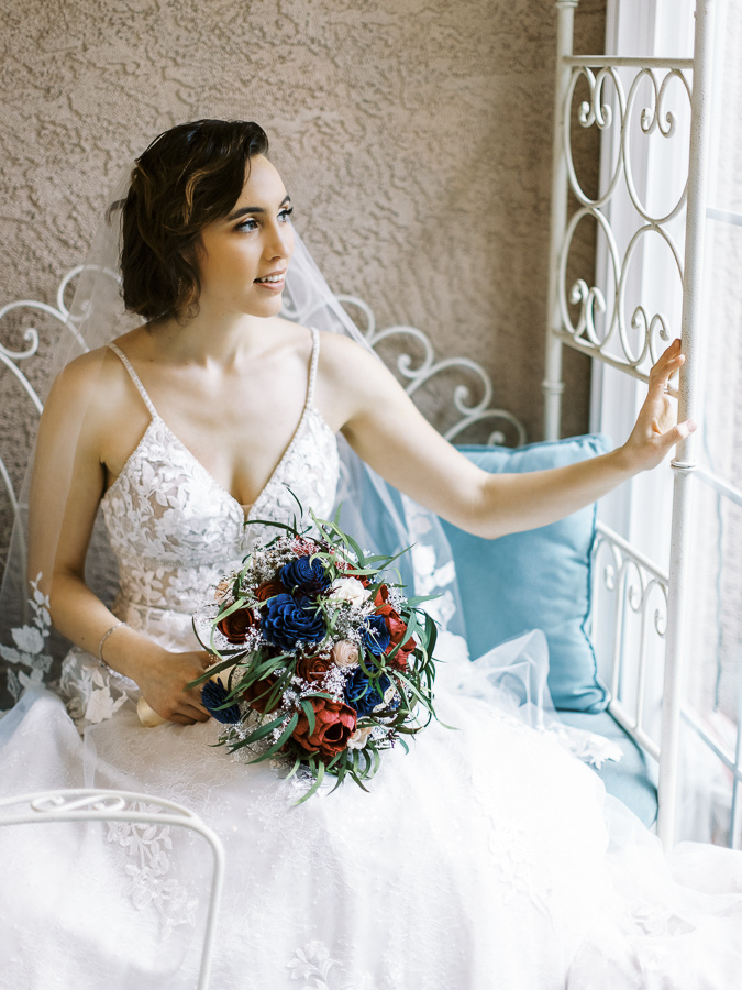 a bride poses next to a window before her Bay Area intimate wedding