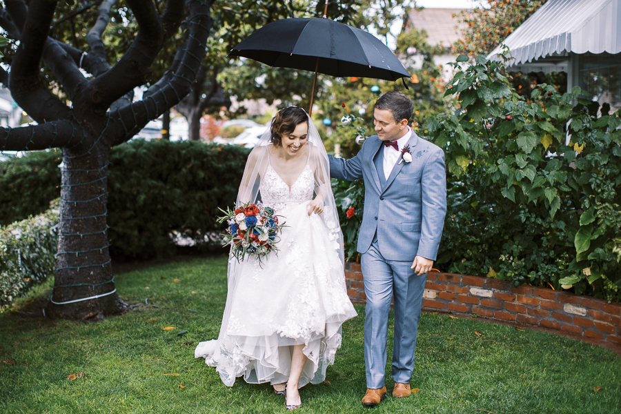 a bride and groom running through the rain after their Bay Area intimate wedding