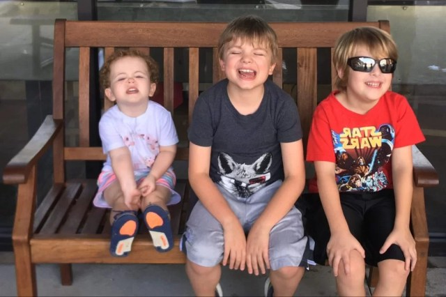 Three smiling children on a bench during a road trip