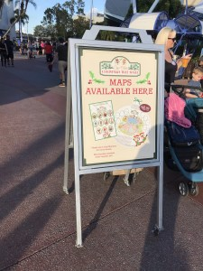 """Christmas Tree Spree Maps Available Here"" sign at Epcot"