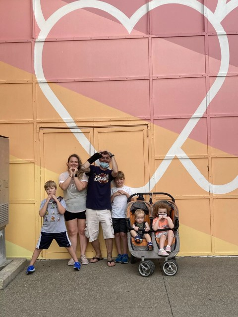 Family of six (with stroller) in front of mural with pink hearts and yellow background at Old Falls Street