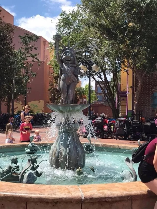 Metal muppets miss piggy holding a torch and dressed as Statue of Liberty Water fountain outside muppet 3d