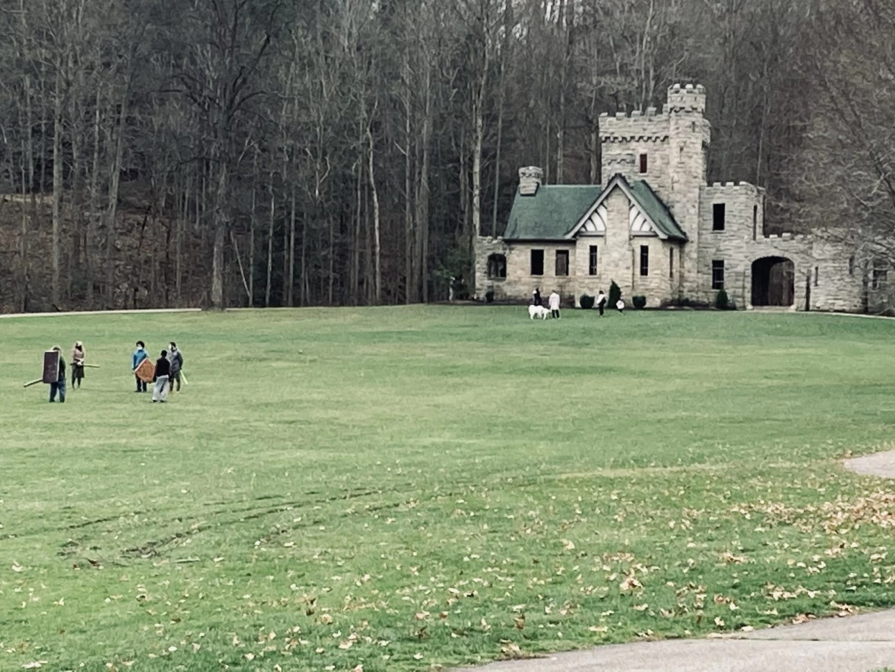 Squire's castle with a group of adults with shields and swords out front on the grass