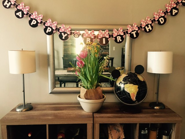 A minnie mouse banner in front of a mirror and flowers with a mickey mouse ear globe