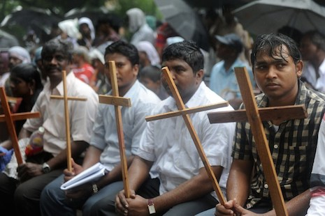 <p>Indian Dalit Christians and Muslims sit in the rain during a 2012 protest in Delhi (AFP Photo/Raveendran)</p>