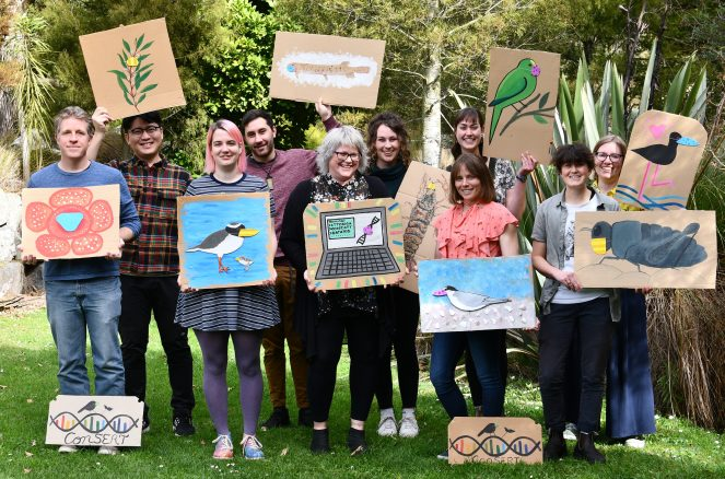 A group photo of ten of the members of ConSERT 2020, holding artworks of their focal species, where the organisms are wearing face masks.