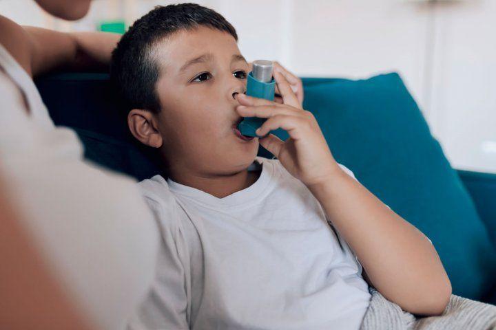 Niño sentado en el sofá con un inhalador