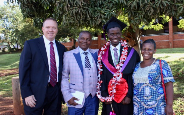 Mark Bartels, UCU Partners Executive Director, left, with Bwambale Bernard Mulcho with his parents at his October 2018 graduation day. (UCU Partners Photo)