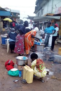 Women make and sell popcorn and other snacks along a walk path in Arua City