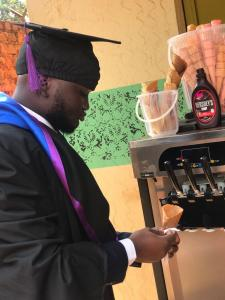 Reagan Moses Muyinda, graduation gown, treats himself at his ice cream stall on the day he graduated on December 18, 2020.