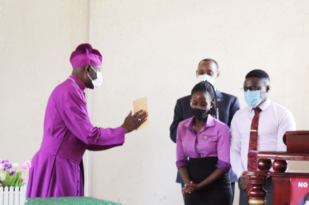 The Archbishop, His Grace the Most Rev. Dr. Samuel Stephen Kaziimba Mugalu (left), receives donation from UCU student leaders, led by Guild President Kenneth Amponda (right). Behind them is Vice-Chancellor Aaron Mushengyezi.
