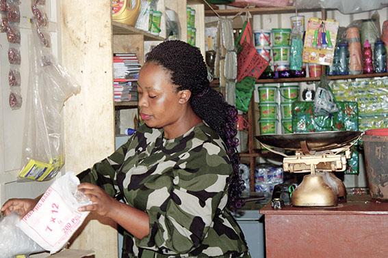 Charlotte Mbabazi attends to a customer in her shop on Wandegeya-Bugujju Road.