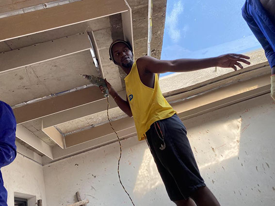 Nasasira fixes a board ceiling during a renovation at client's residence