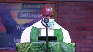 Eng. Rev. Paul Wasswa preaches during community worship in Nkoyoyo Hall.
