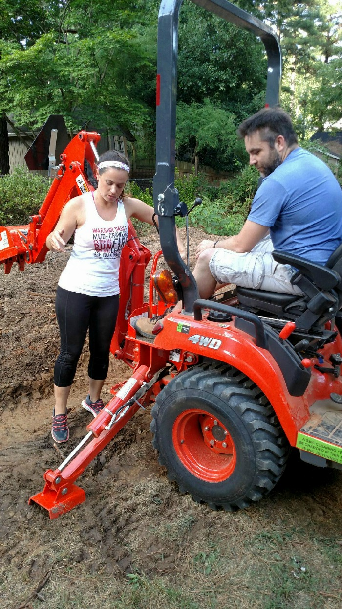 teaching friends how to use a small backhoe