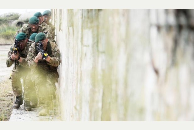 This image might look like a real-life assault on a enemy position, but it was in fact taken during the opening stages of an annual training exercise.