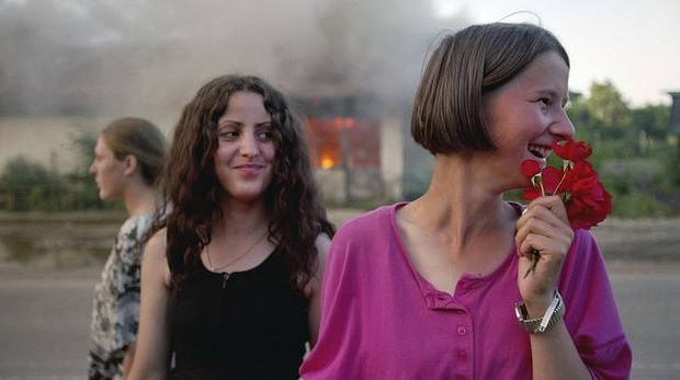 Kosovo Albanian girls celebrate freedom in front of a burning house, 12 June 1999. Photo: Alexandra Boulat