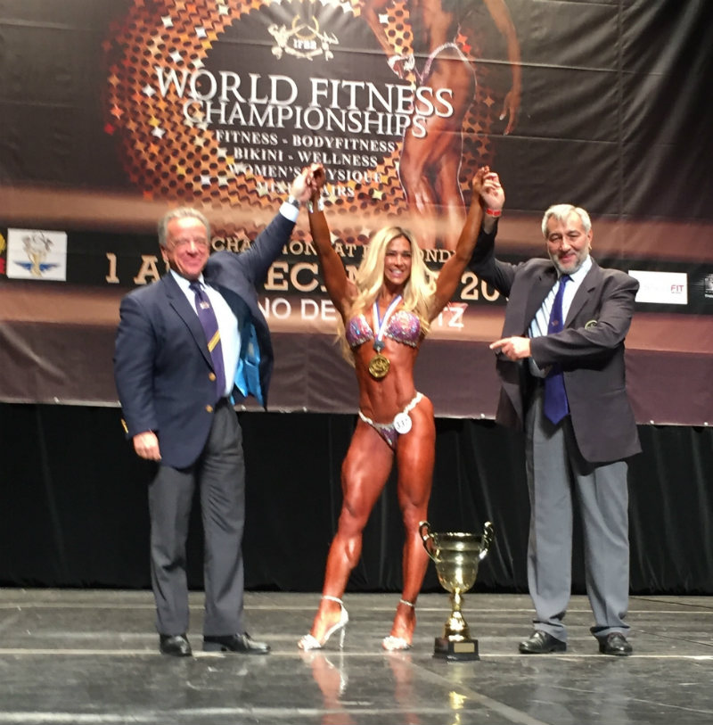 Gentiana Beqa of Kosovo displays the trophy as overall IFBB world champion in the women's wellness fitness category, flanked by IFBB President Rafael Santonja, left, and Mario Valero, President of the French Bodybuilding and Fitness Association