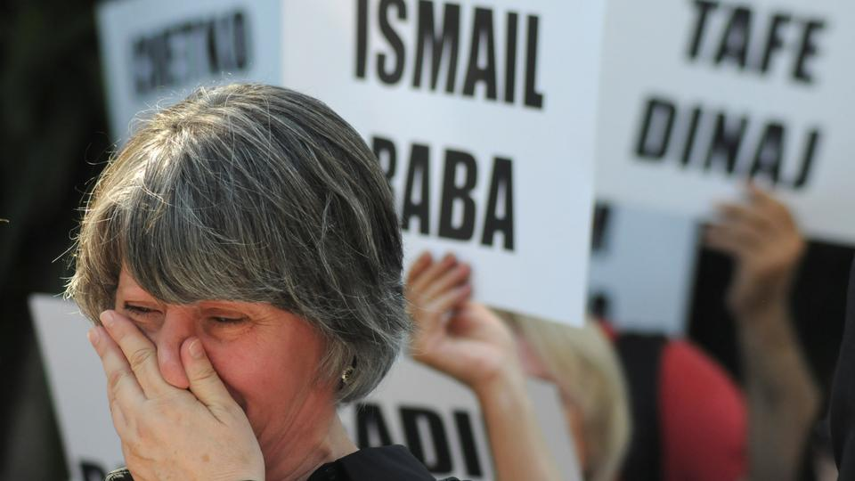 "A woman cries as people hold names of missing persons marking the ""International Day of the Disappeared"", in Pristina, Kosovo, August 30, 2018. (Reuters)"