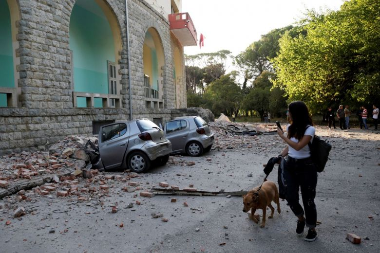 A woman with a dog walks past destroyed cars and a damaged building after an earthquake in Tirana.PHOTO: REUTERS