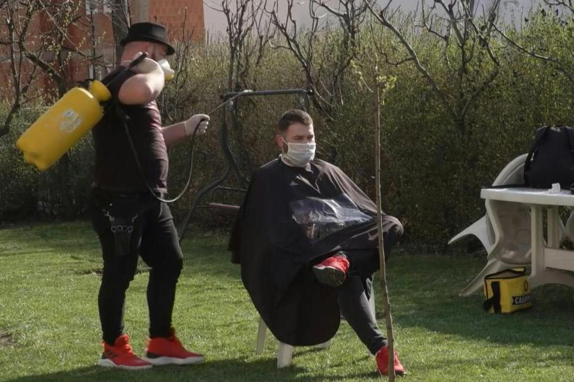 Equipped with a mask, gloves and tank of disinfectant spray, a popular Pristina barber has taken his show on the road to clip and coif clients who are stuck at home under coronavirus lockdown.