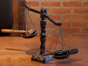 scale of justice weighing judge's gavel and a gun