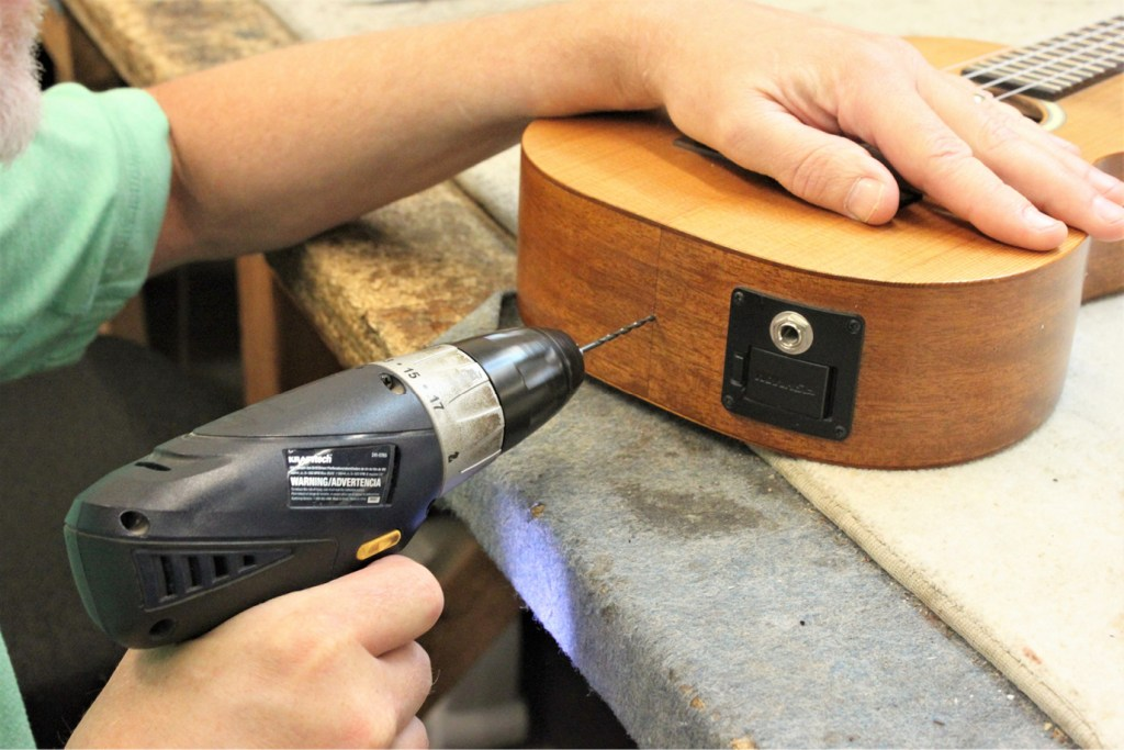 how to install a ukulele strap, drilling the pilot hole on the end of the ukulele
