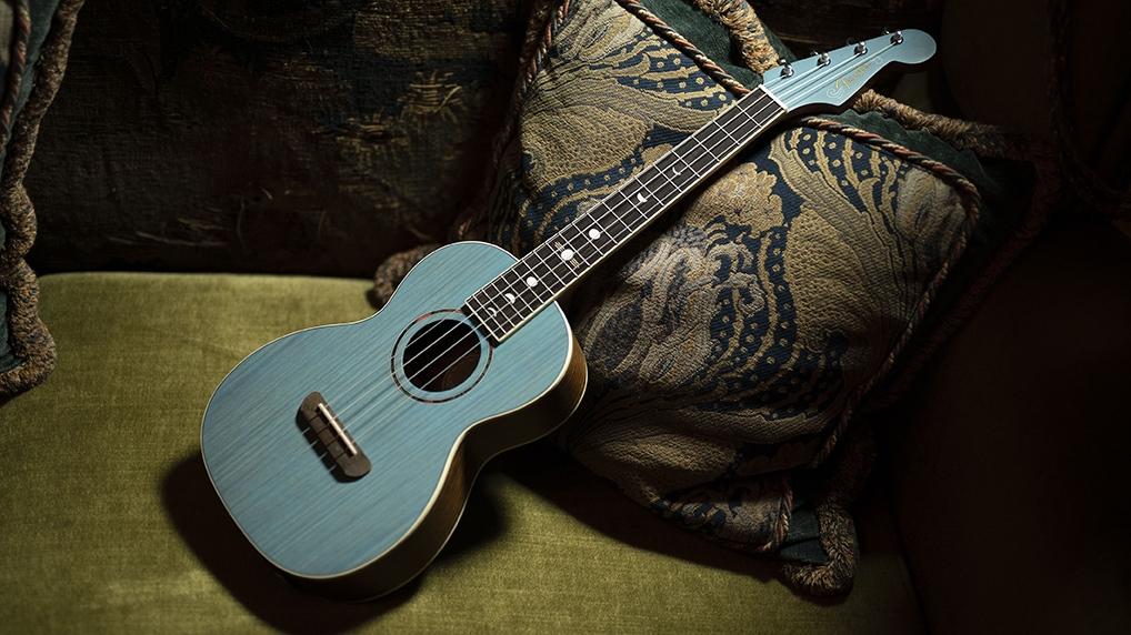 turquoise blue dhani harrison signature fender tenor ukulele displayed on a a plush background