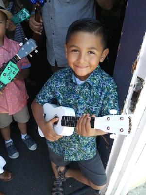 Smiling young student holding ukulele