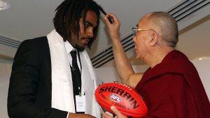 Harry O'Brien entrega uma bola de futebol australiano para o Dalai Lama...