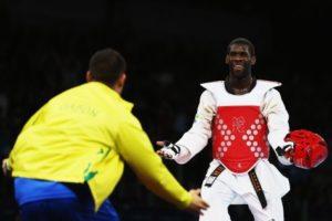 Gabonês celebra com o técnico após vencer luta em Londres-2012