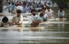 A man wades through waist deep waters with his child while escaping floods in Risalpur, located in Nowshera District, in Pakistan's Northwest Frontier Province July 30, 2010. About 150 people have been killed by flashfloods and bad weather in Pakistan in the last week, with the country's northwest and Baluchistan provinces bearing the brunt of the storms, officials said on Thursday.  REUTERS/Adrees Latif  (PAKISTAN - Tags: DISASTER ENVIRONMENT)