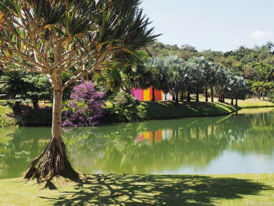"Reflections in a pond at Inhotim: tropical vegetation, and the colourful walls of the ""Magic Square"" by Hélio Oiticica in the background."