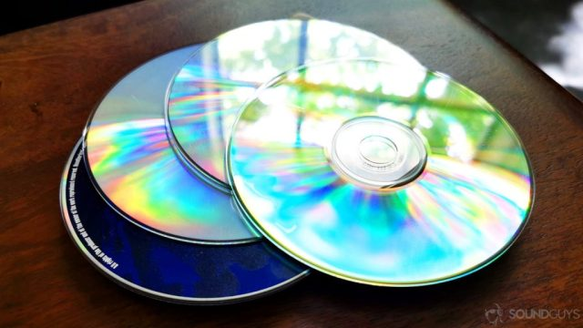 A photo of CDs on a wooden table.