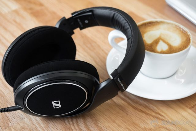 A photo of the Sennheiser HD 598 CS leaning against a cappuccino on a light-colored wood table.