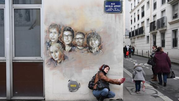 """Une passante prend un selfie devant les portraits des victimes de l\'attentat de \""""Charlie Hebdo\"""", peints sur la facade d\'un bâtiment de la rue Nicolas-Appert, le 7 janvier 2018."""