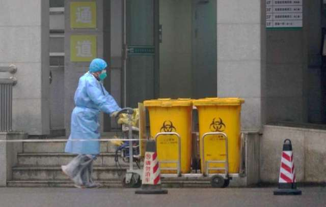 Un employé déplace des biodéchets dans l'hôpital de Wuhan où des patients contaminés par le virus sont traités, le 22 janvier.