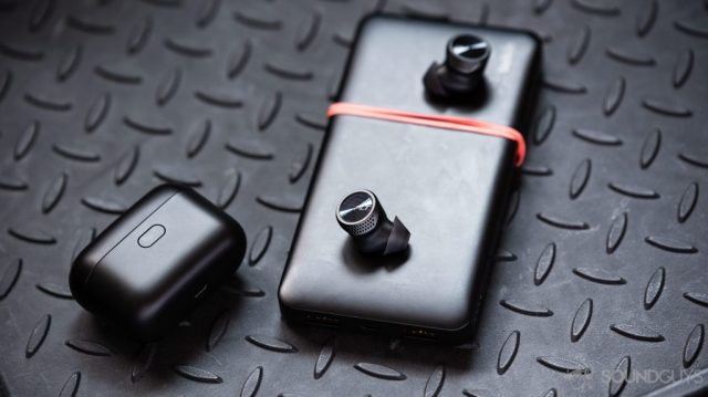 A picture of the Plantronics BackBeat Pro 5100 true wireless earbuds outside of the case (closed) atop a Belkin battery pack.