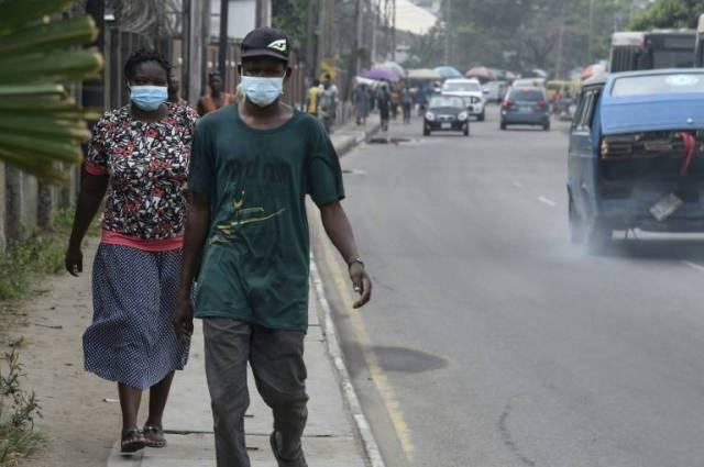 Des passants protégés par des masques dans un quartier de Lagos, le 28 février 2020 ( AFP / PIUS UTOMI EKPEI )