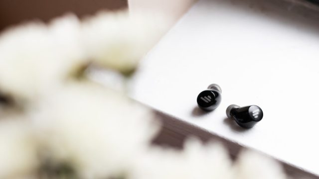 A photo of the Edifier TWS1 true wireless earbuds on a windowsill with flowers in the foreground.