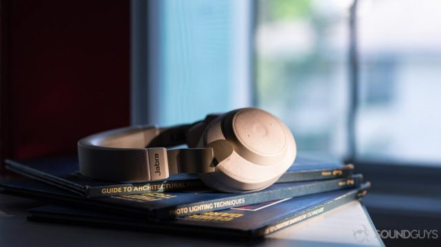 A photo of the Jabra Elite 85h headphones in front of a window on a stack of books.
