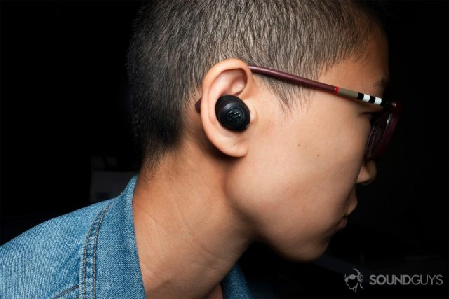 A picture of a woman wearing the JLab JBuds Air true wireless earbuds.
