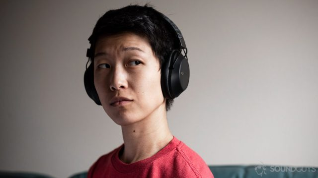 A picture of the Plantronics BackBeat Fit 6100 workout headphones worn by a woman against an off-white wall.