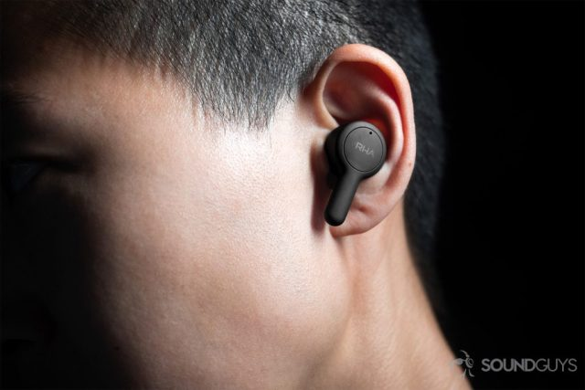 A picture of the RHA TrueConnect true wireless earbuds (left) being worn by a woman, it protrudes a bit from the ear with the stem angled downward.